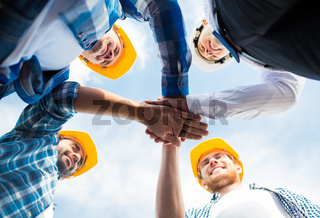 close up of builders in hardhats with hands on top