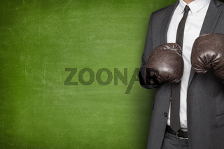 Businessman in boxing gloves on blackboard background
