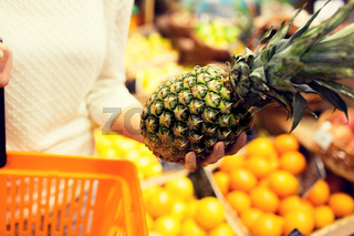 close up of woman with pineapple in grocery market