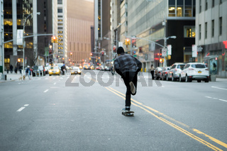 Back figure of young skateboarder cruising donw the city street before sunset.