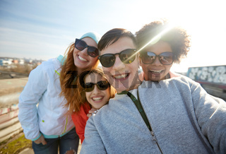 group of happy friends taking selfie on street