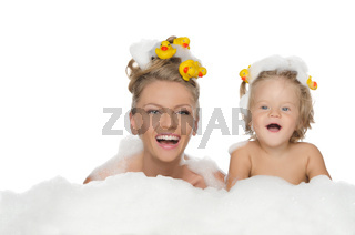 Young mother, daughter with ducks and soap foam
