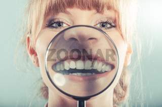 Woman smiling showing teeth with magnifying glass