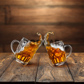 splash of beer in glasses on wood