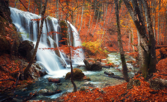 Waterfall at mountain river in autumn forest at sunset.