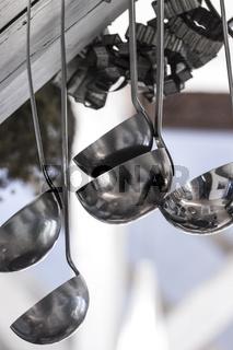 Verschiedene Schöpfkellen hängen in der Küche
