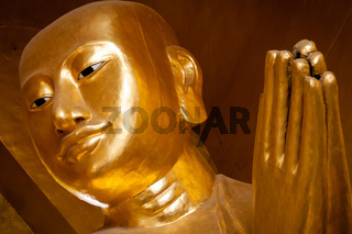 Close-up of a praying golden buddha