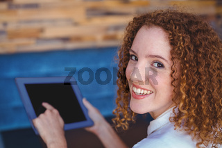 Pretty girl using a small tablet at table