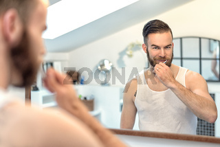 Mann mit Bart putzt seine Zähne