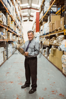 Smiling warehouse manager writing on clipboard