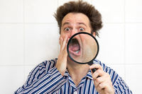 frightened man in pajamas watching his face magnifying glass
