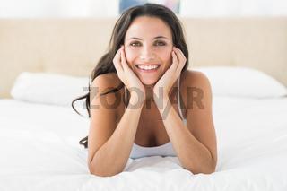 Happy brunette lying on bed