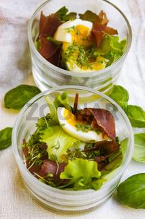Gekochte Eier mit Pflücksalat, Parmaschinken und Kresse im Glas