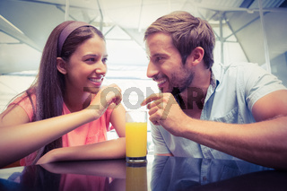 Young happy couple sharing a drink