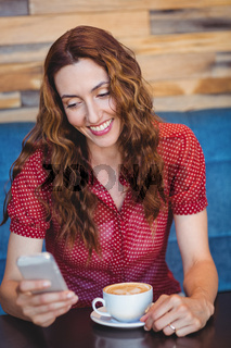 Woman using her mobile phone and holding cup of coffee