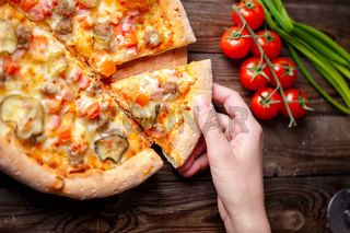 Hand picking tasty slice of pizza lying on wooden table