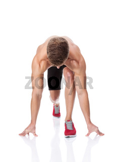 Muscular man in start position ready for the race