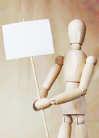 Wooden man model holding blank white poster in its hands. Concept of claims