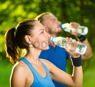 Man and woman drinking water from bottle after fitness sport exercise