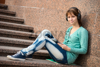 Beautiful young woman student with note pad and headphones. Outdoor student.