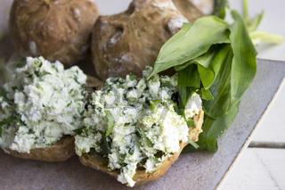Bärlauch-Frischkäse auf Bio-Brötchen mit Bärlauchblättern