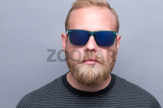 Serious bearded man in sunglasses
