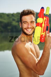 Mann hat Spaß im Sommer mit Wasserpistole