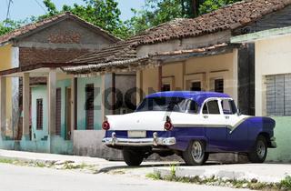HDR blauer Oldtimer parkt vor einem Haus im Landesinneren von Kuba