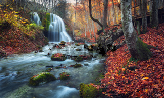 Beautiful waterfall in autumn forest in crimean mountains at sunset