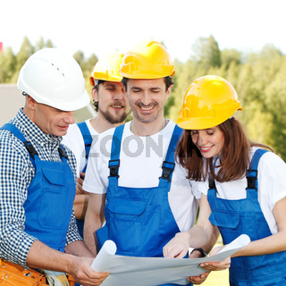 Team of workers look at blueprint