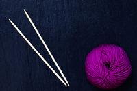 pink Wollknäuel auf schwarzer Schieferplatte mit Stricknadeln aus Bambus
