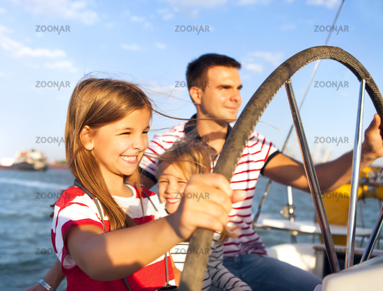 Young father with adorable daughters on a big boat