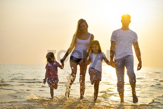 Happy young family having fun running on beach at sunset. Family traveling concept