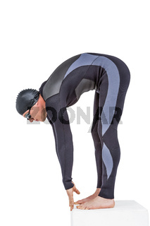 Swimmer in wetsuit preparing to dive