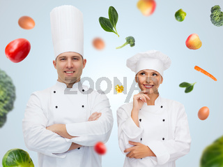 happy chef couple or cooks over food background