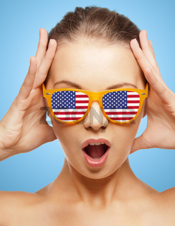 happy teenage girl in shades with american flag