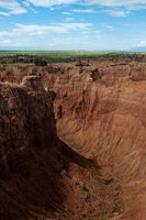 Steep cliff and valley of red orange sand stone rock formation in hot desert Tatacoa under blue sky, Huila