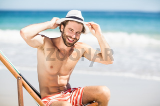 Man sitting on armchair at beach
