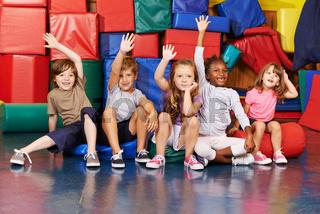 Kinder heben Hände in der Turnhalle