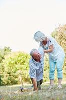 Frau hilft einem alten Mann mit Hexenschuss