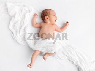 Cute newborn baby lying on bed under a blanket