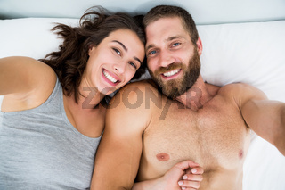 Portrait of couple smiling on bed