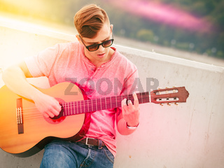 Trendy guy with guitar outdoor
