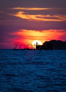 Sailboat and lighthouse on dramatic sunset