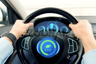 close up of young man driving car in eco mode
