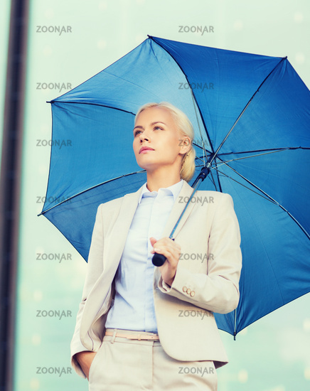 young serious businesswoman with umbrella outdoors