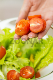 close up of woman cooking vegetable salad at home