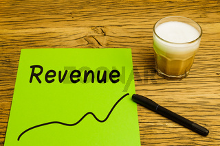 Revenue written on green paper with graph. Marker and coffee on desk.