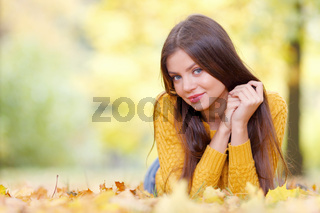 Brunette woman laying in autumn park