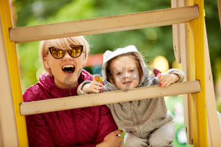 Mother and daughter playing on the playground outdoors